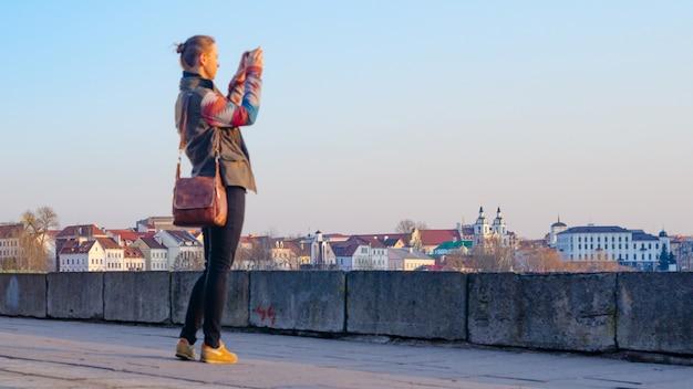 Молодая женщина фотографирует город на смартфоне
