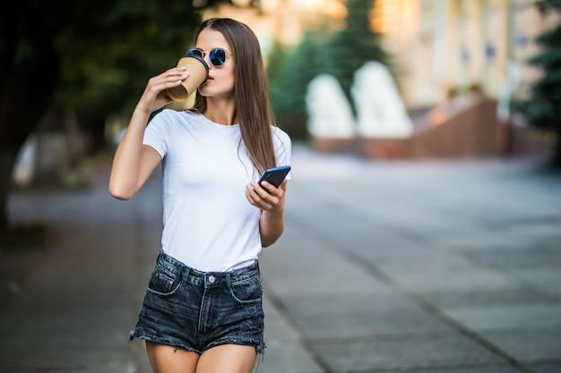 若い女性がコーヒーブレークをとり、通りでスマートフォンを使用して