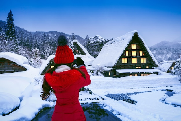 Молодая женщина фотографирует в деревне сиракава-го зимой, япония.