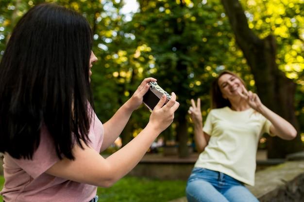 若い女性が彼女の友人の写真を撮る