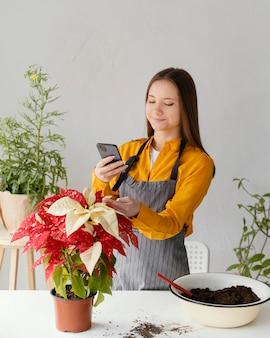 Молодая женщина фотографирует свое растение