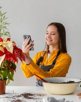 그녀의 식물의 사진을 복용하는 젊은 여자