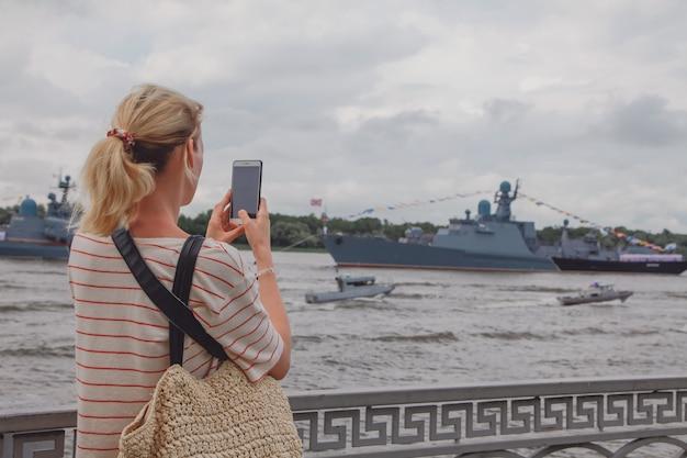 Молодая женщина фотографирует военные корабли на волге в россии. русские военные корабли в реке волга в астрахани летом в пасмурный день. российские военные корабли.