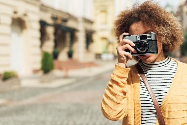 Молодая женщина, делающая фото с камерой с копией пространства
