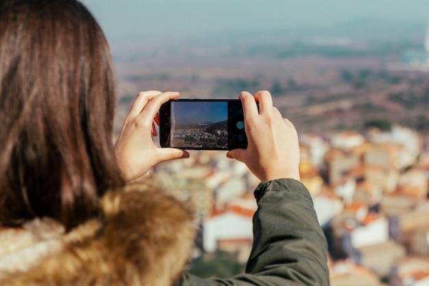 Молодая женщина берет фотографию со своего смартфона