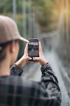 스마트폰으로 다리 사진을 찍는 젊은 여성