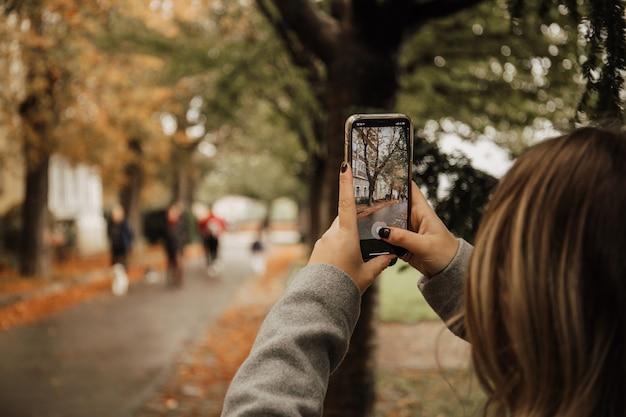 Молодая женщина фотографирует с помощью смартфона