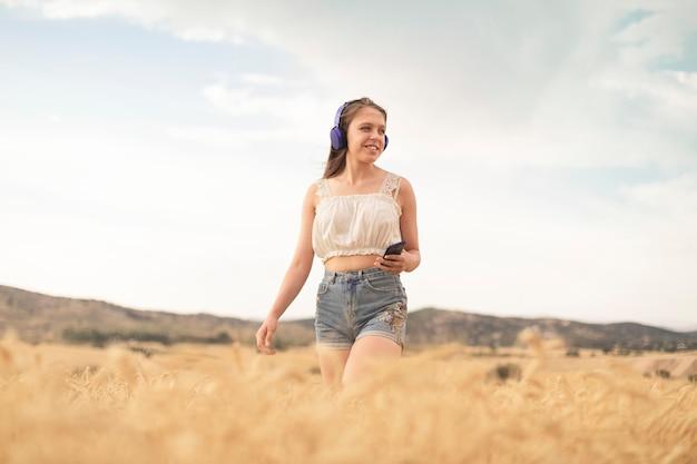 音楽を聴きながら日没で麦畑をくつろぐ散歩をしている若い女性