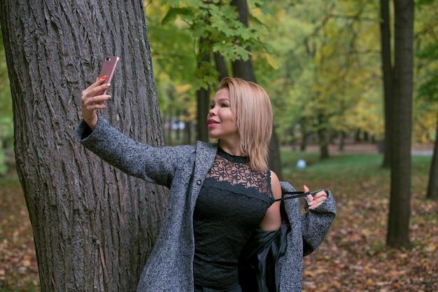 Молодая женщина, принимая селфи в парке