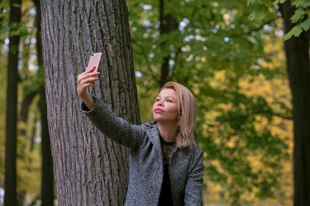 Молодая женщина, делающая селфи в парке