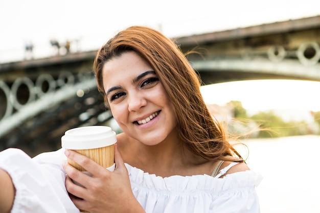 コーヒーを飲みながら自分撮りをしている若い女性スペインのセビリアの川で写真を撮っている女性