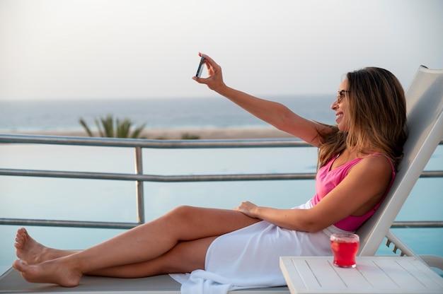 Молодая женщина, делающая селфи со своим смартфоном в отпуске