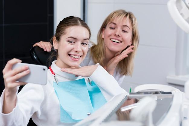 Молодая женщина, принимая селфи с стоматологом