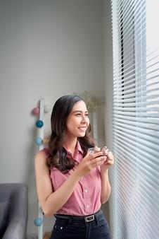 사무실 창에 의해 서 차 휴식을 복용하는 젊은 여자.