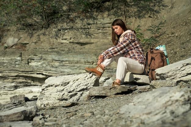 国立公園でのハイキング中に休憩を取っている若い女性