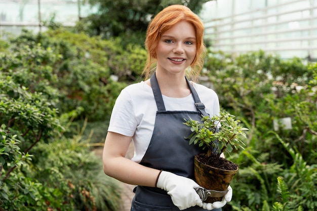 Young woman taking care of her plants in a greenhouse