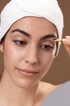 眉毛の世話をする若い女性