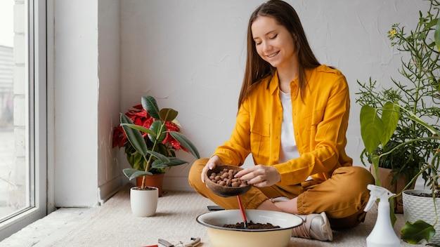 집에서 그녀의 식물을 돌보는 젊은 여자