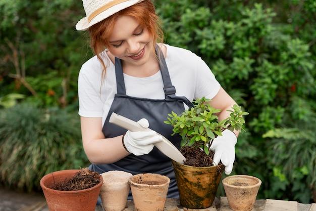温室で彼女の植物の世話をしている若い女性
