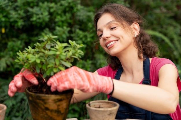 Молодая женщина заботится о своих растениях в теплице