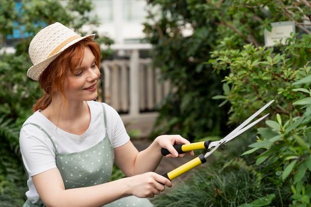 그녀의 식물을 돌보는 젊은 여자