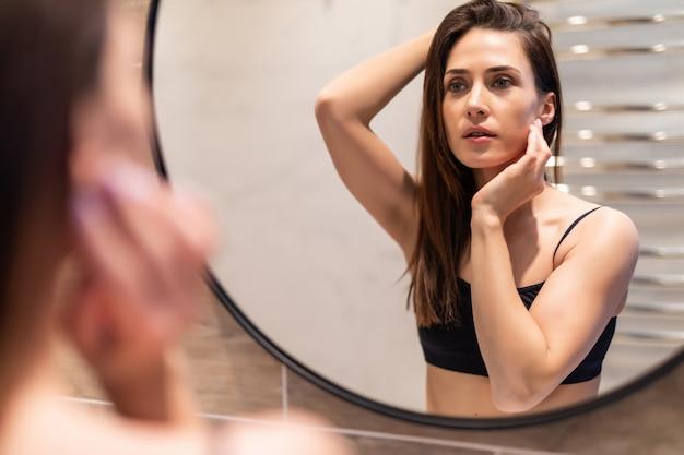 Молодая женщина заботится о своей коже перед зеркалом в ванной комнате