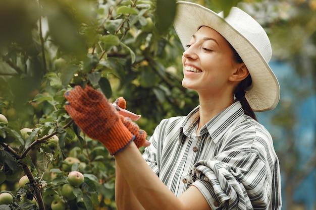 植物の世話をする若い女性。帽子と手袋のブルネット。女性はaveeuncatorを使用します。