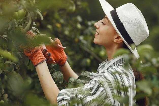 植物の世話をする若い女性。帽子と手袋のブルネット。