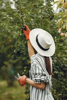 Giovane donna che si prende cura delle piante. bruna in un cappello e guanti. donna usa aveeuncator.