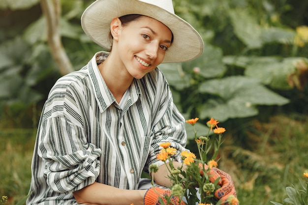 Young woman taking care of plants. brunette in a hat and gloves.