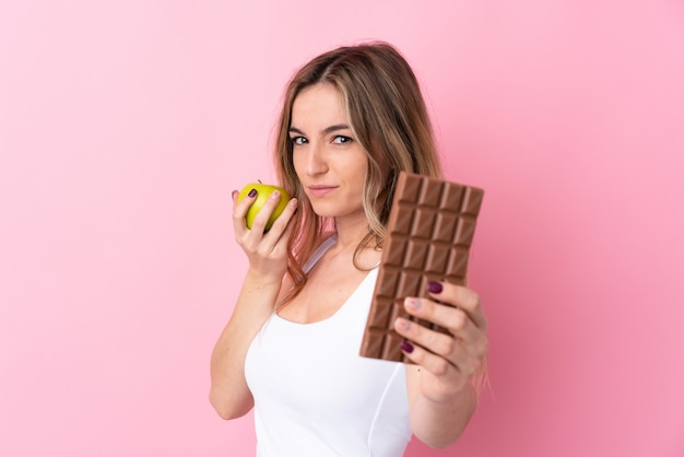 Young woman taking a chocolate tablet in one hand and an apple in the other