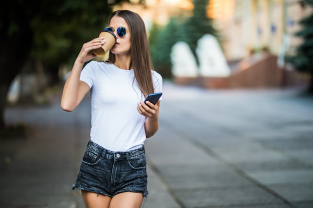 Young woman taking a coffee break and using smartphone in the street