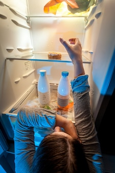 Young woman taking donut from top shelf of refrigerator