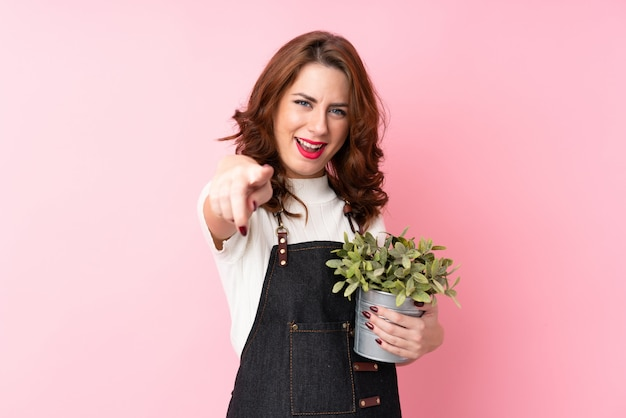 Young woman taking a flowerpot and pointing to the front
