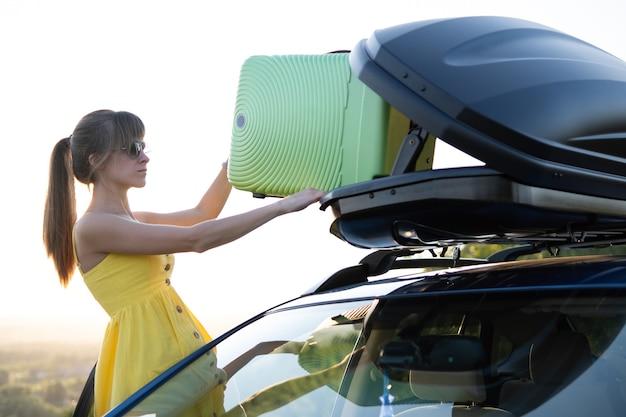 車のルーフラックから緑のスーツケースを取る若い女性。旅行と休暇のコンセプト。