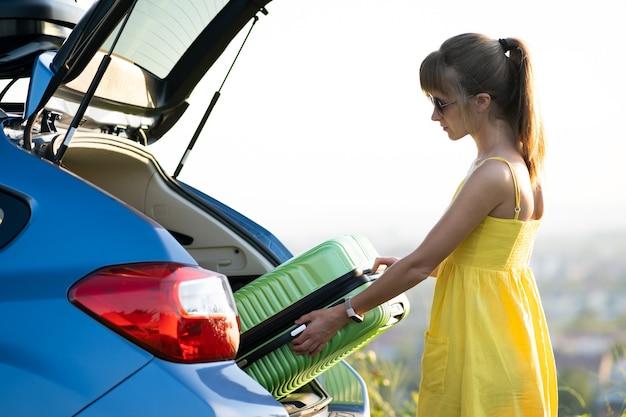 車のトランクから緑のスーツケースを取る若い女性。旅行と休暇のコンセプト。