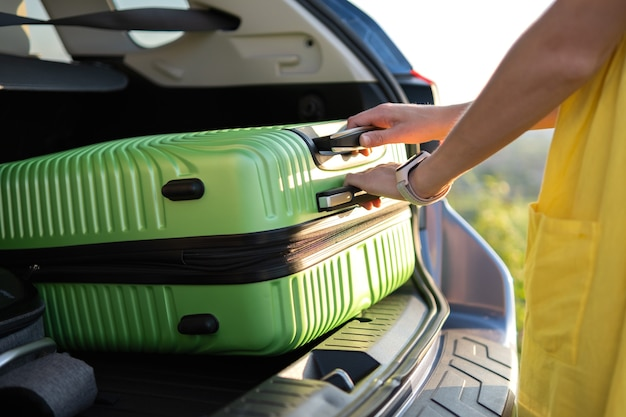 Young woman taking green suitcase from car trunk. travel and vacations concept.