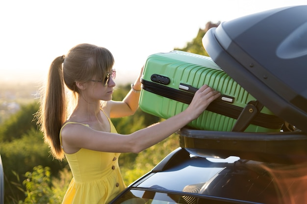 Young woman taking green suitcase out from car roof rack. travel and vacations concept.