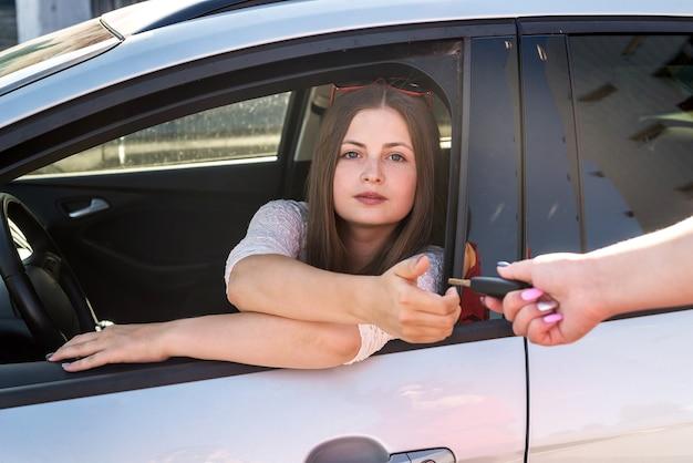 Молодая женщина берет ключи от арендованной машины