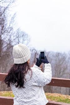 Молодая женщина, делающая пейзажные фотографии со своим смартфоном