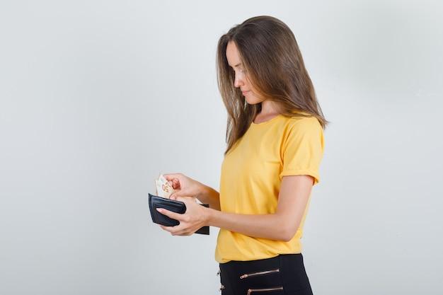 Молодая женщина берет деньги из бумажника в желтой футболке