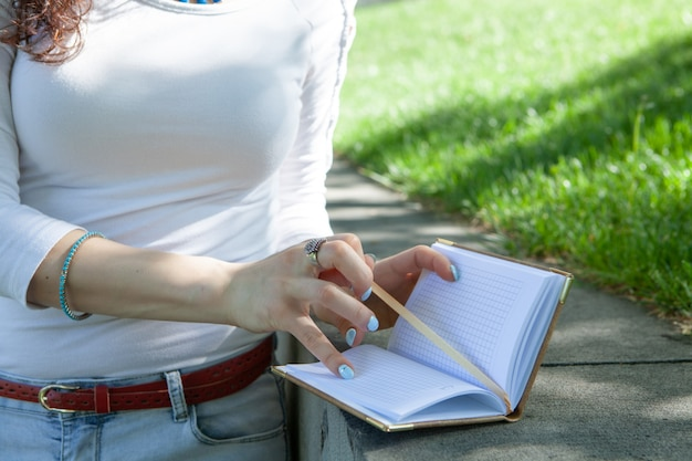 Young woman taking notes in a notebook in the park