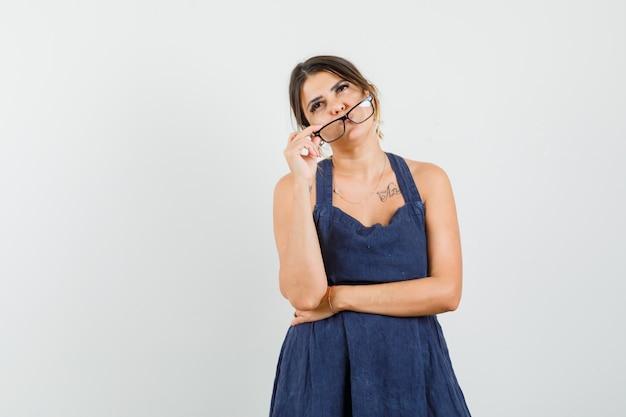 ドレスを着て眼鏡を脱いで物思いにふける若い女性