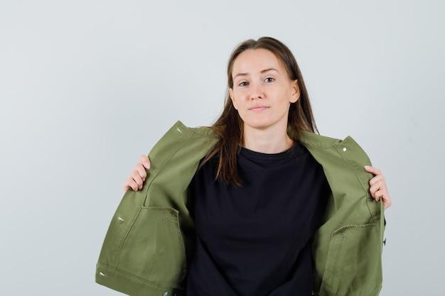 Giovane donna che toglie la sua giacca in giacca verde, vista frontale.