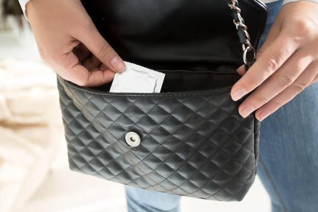 지갑에서 포장 된 콘돔을 복용하는 젊은 여자