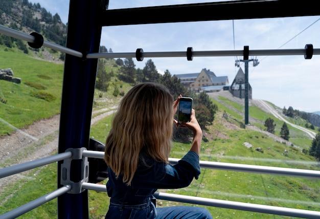 Giovane donna che scatta una foto di una bella vista