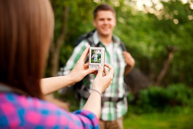 彼女のボーイフレンドのために写真を撮る若い女性