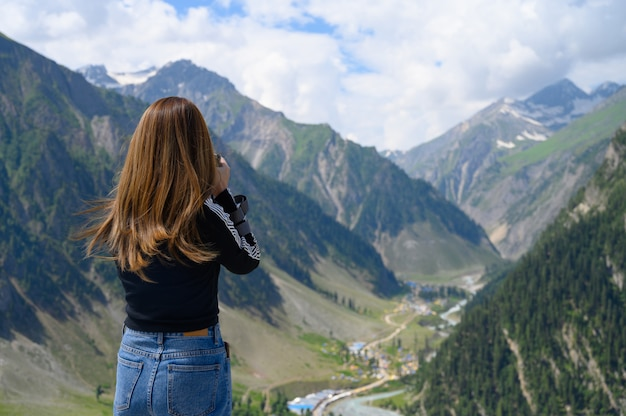 Young woman taking photo of mountain