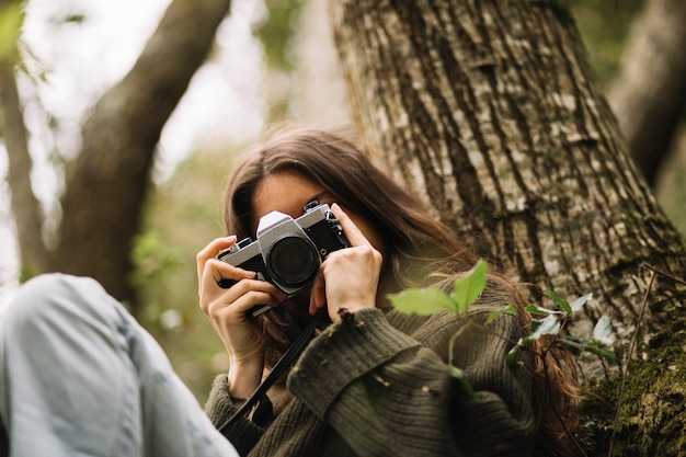 Young woman taking photo in nature