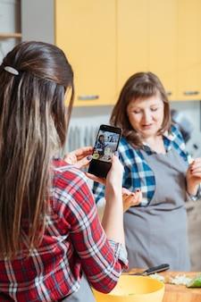 Молодая женщина фотографирует другую женщину на кухне во время готовки